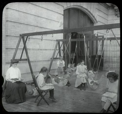 Women and girls reading near swingset where younger children are suspended in hammock like swings, July 1910.