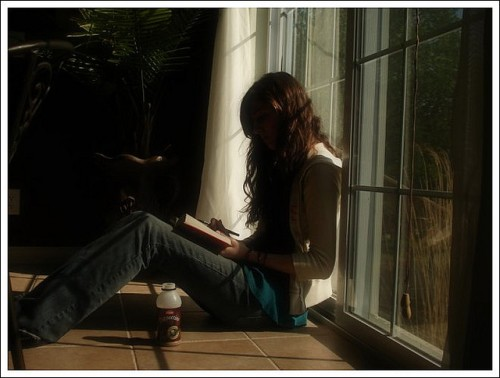 Teenager reading by window